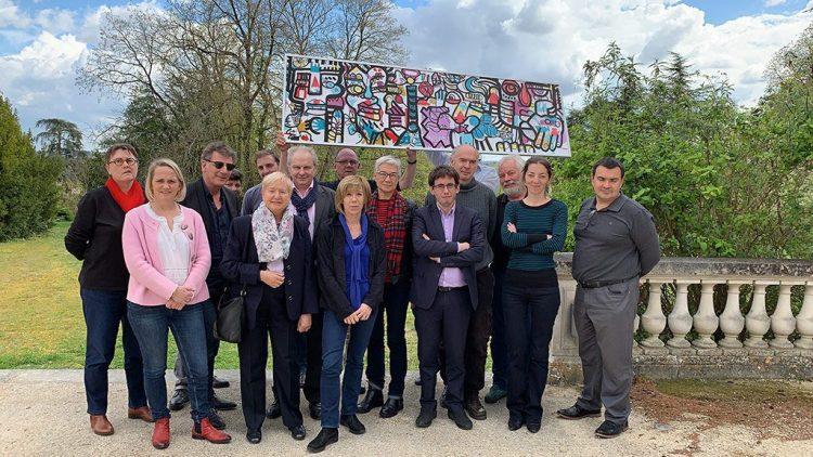 un groupe tient un tableau conçu en team building fresque commune disponible sur salon préventica