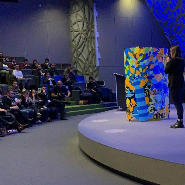 Une personne sur scène devant un publique en assemblée présente le résultat d'une animation Convention Animation Fresque Totem Box XL Tube plexi My Art Box