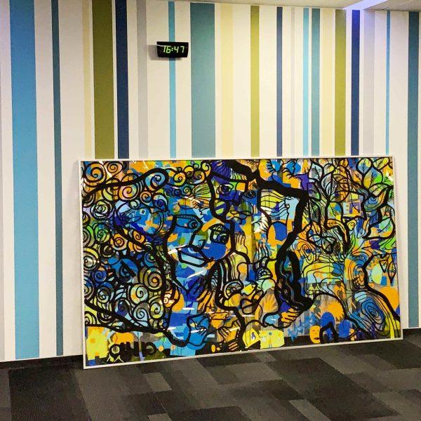 Une fresque géante Totem box XL graffiti plexi encadré et posé devant un mur à rayures du siège d'une société de Rouen après une animation de séminaire avec 200 participants