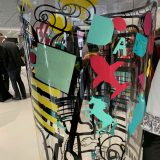 Des formes et symboles colorés collés sur un Tube plexi géant de l'artiste aNa lors d'une Animation Fresque My Art Box en cocktail à Grenoble