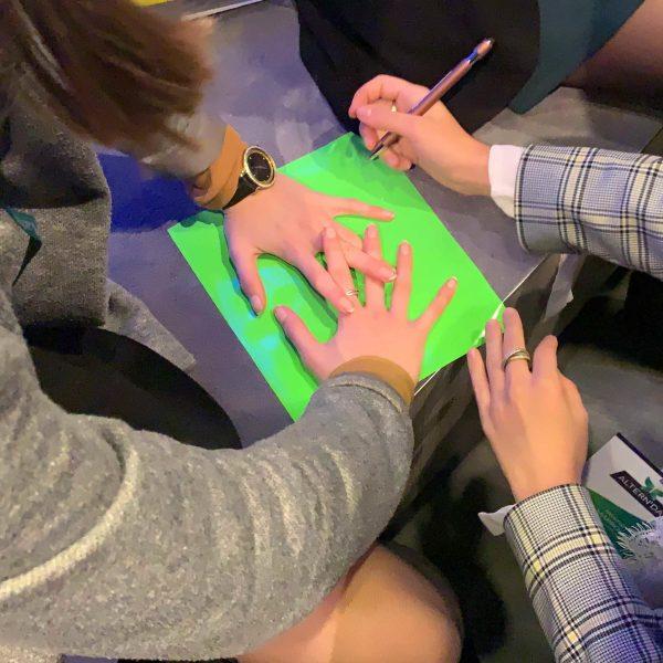 Des jeunes femme en gros plan sur leurs mains en train de découper le contour de leurs doigts pour représenter l'idée animation cohésion lors d'une animation fresque my art box format Totem Box XL