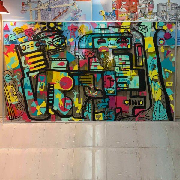Une œuvre encadrée en aluminium Idée Animation Fresque sur plexi. Formes colorées collées sur une plaque géante de plexi transparent et réhaussées par le dessin original de l'artiste aNa à l'encre noir.