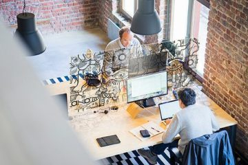 vue de dessus d'un bureau commun occupé par deux hommes dans un loft en briques rouges et séparés par une décoration brise vue puzzle my art box