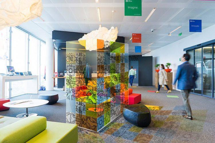 une paroi vitrée décorée de carrés colorés fresque open space installée au milieu d'un hall commun dans une entreprise