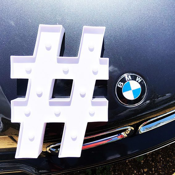 sur une bmw m3 e36 noir un hashtag blanc design posé à coté du logo de la marque BMW pour illustrer comment développer son business avec instagram