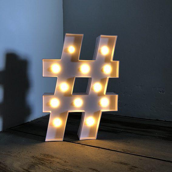 Un hashtag blanc lumineux posé sur un planché en bois dans un angle de murs blancs pour illustrer l'importance de bien choisir son hashtag afin de répondre à la question de comment développer son business avec instagram