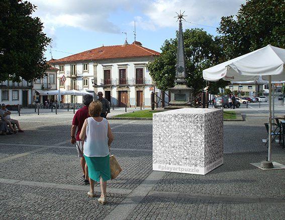 Un homme en polo bordeaux et une femme top blanc jupe verte passent devant un cube dessiné en noir blanc et comportant le hashtag Play Art Puzzle au milieu d'une place publique pavée