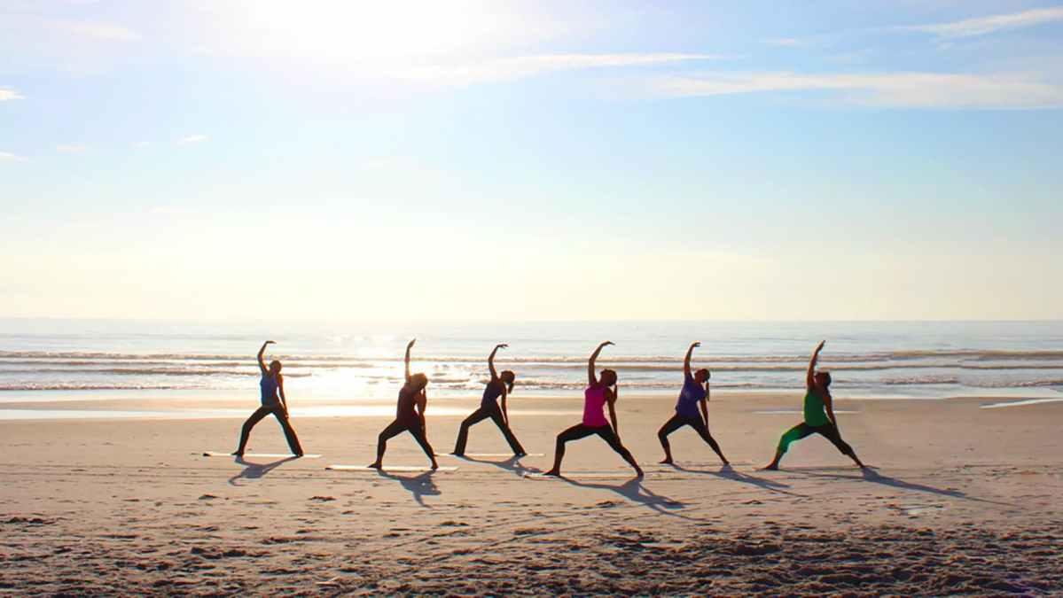 Groupe de personnes pratiquant le yoga sur la plage du Cap Ferret