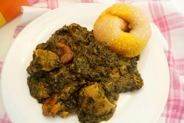 angled overhead shot of ofe onugbu (bitter leaf soup) and eba on a white plate