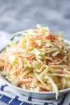 homemade coleslaw in a bowl placed on a napkin