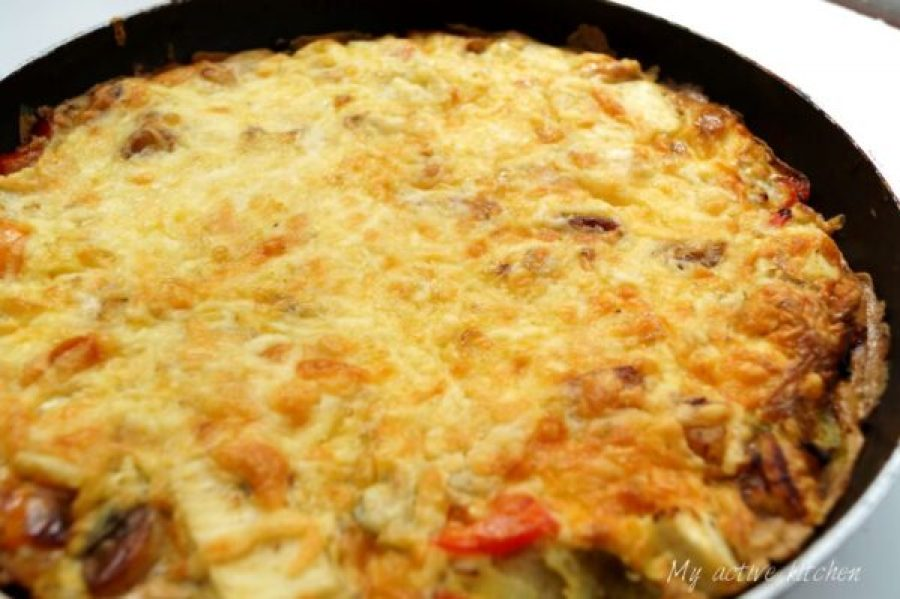 image of uncut plantain frittata still in a pan. Frittata has cheese topping