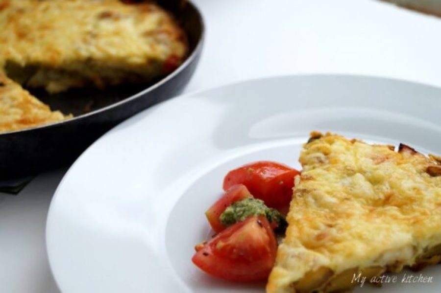 angled shot of frittata wedge served with sliced tomatoes and pesto