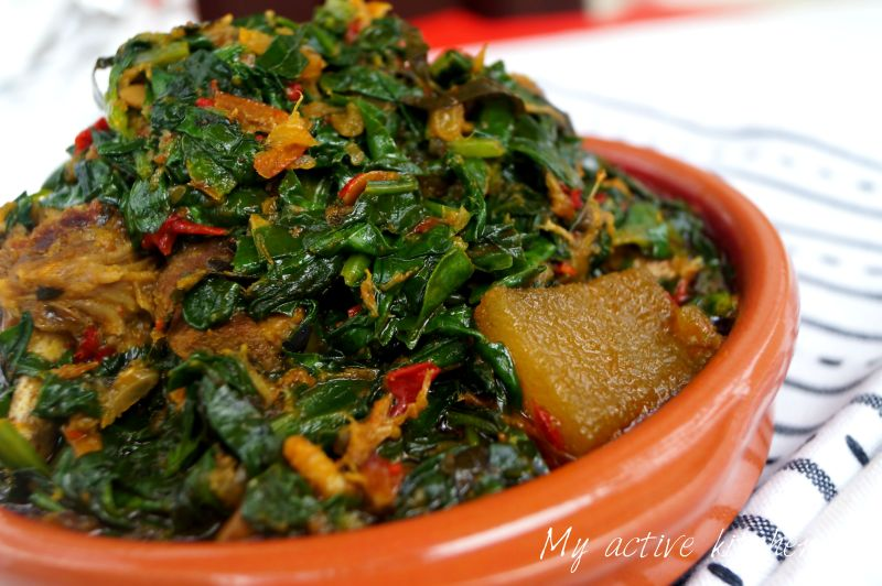 angled shot of efo riro in a brown ceramic bowl placed on a napkin