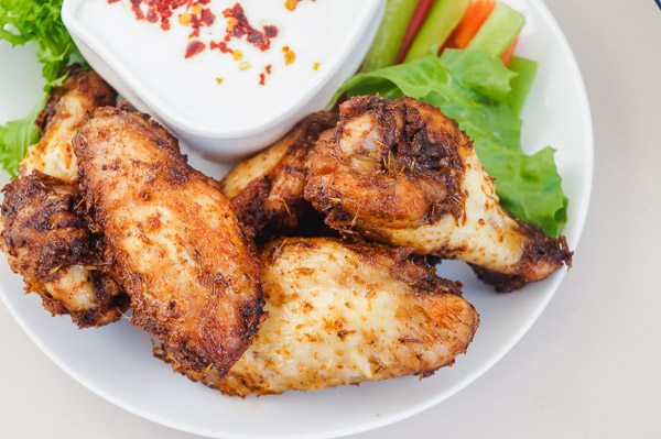 a small plate of easy chicken wings with sliced peppers, lettuce and yogurt dip