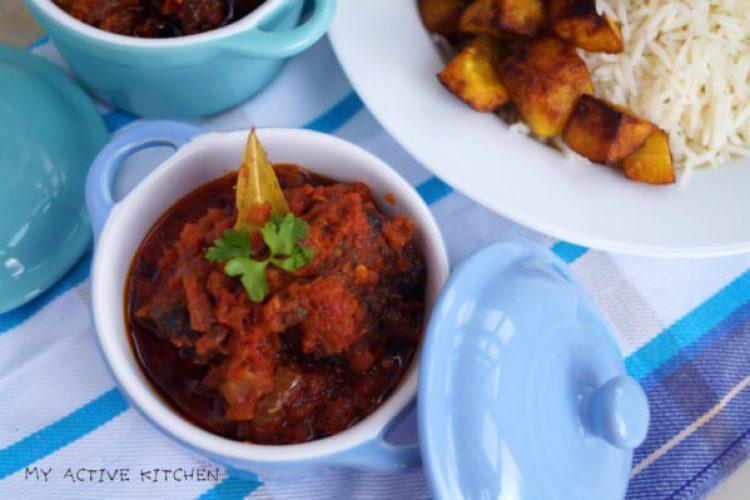 nigerian stew on a blue ramekin, garnished with parsley and dried bay leaf