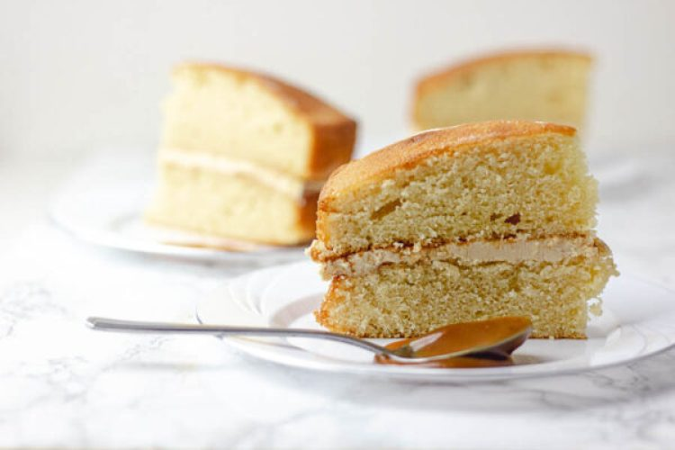 easy sponge cake recipe on a plate with spoon and caramel sauce