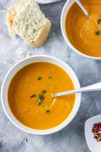 Thick and creamy healthy carrot leek soup served in two white bowls and garnished with fresh thyme. Ready to be eaten with a crusty bread roll on the side