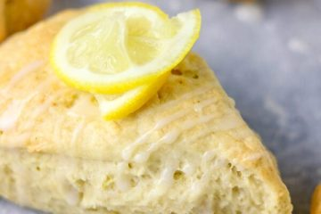a close shot of triangular scone with a rind of lemon as garnish
