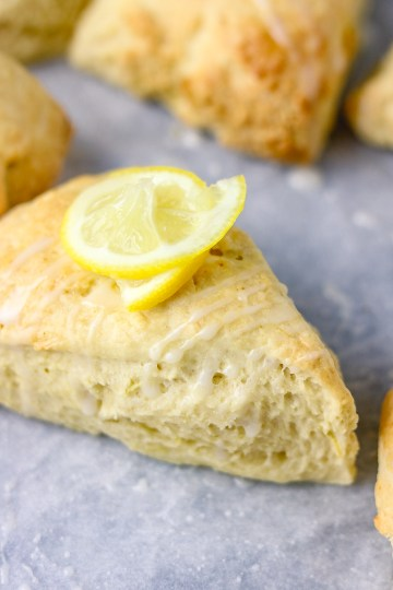 a close shot of lemon scone with a rind of lemon as garnish