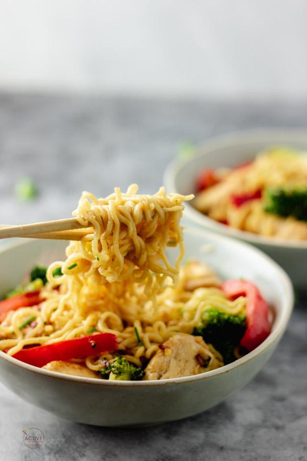 ramen noodle stir fry on a chop stick.