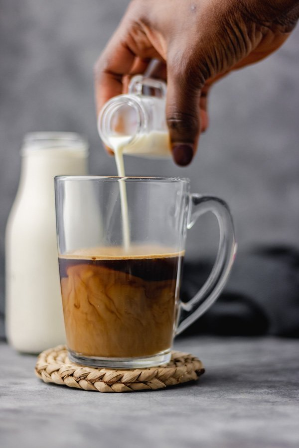 coffee creamer being poured over a cup of coffee.