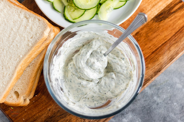 cucumber sandwich filling in a bowl with slices of soft white bread and cucumber slices on a board.