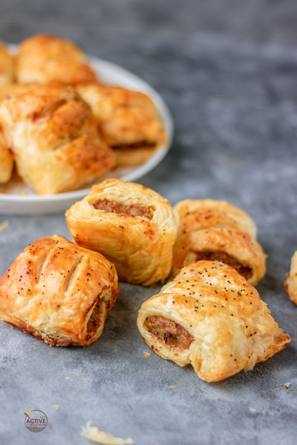 Mini sausage rolls on a blue table.