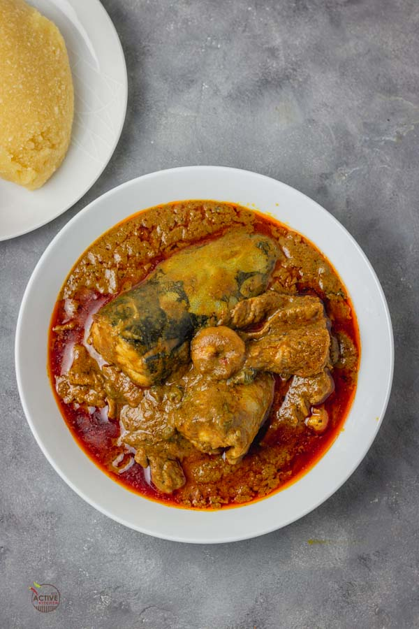 Banga soup cooked with fresh fish, shrimps and periwinkle, it is served with Nigerian eba.