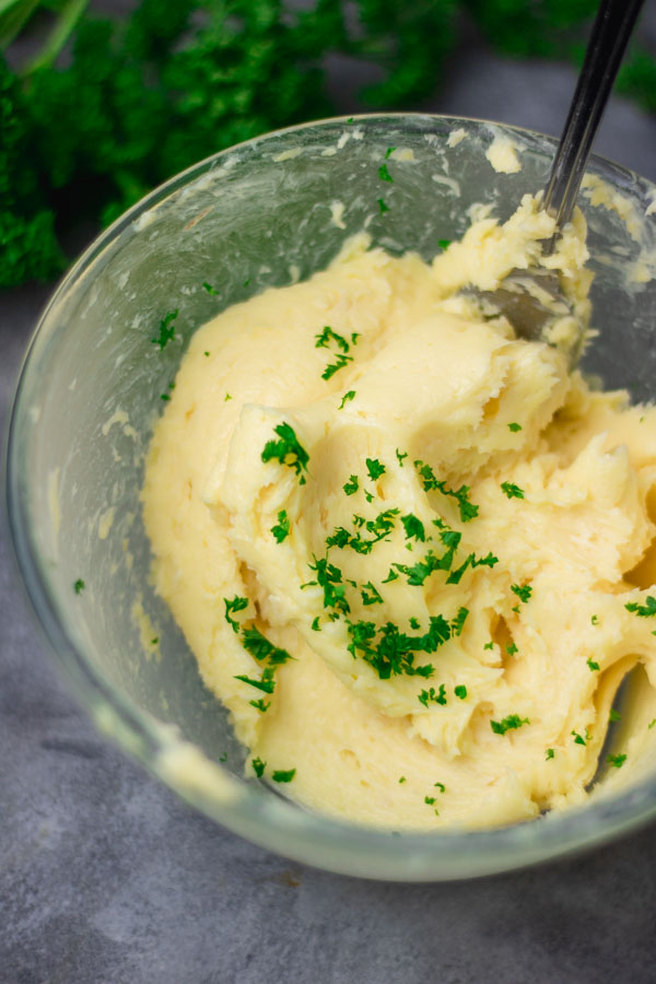 freshly mixed roasted garlic butter with chopped parsley in a bowl.