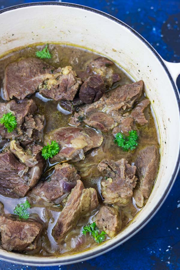 pot of cooked meat garnished with parsley.