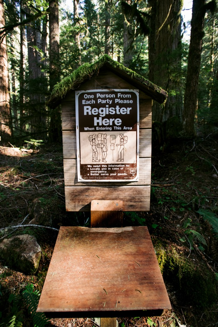 Trailhead register draped in moss