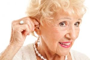 Senior Woman Inserts Hearing Aid