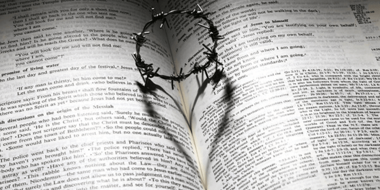 crown of thorns with shadow of heart on a page of scripture