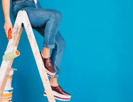 A girl sitting on a ladder with a paint roller in hand with a blue wall behind her