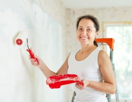 An older woman happily painting a wall