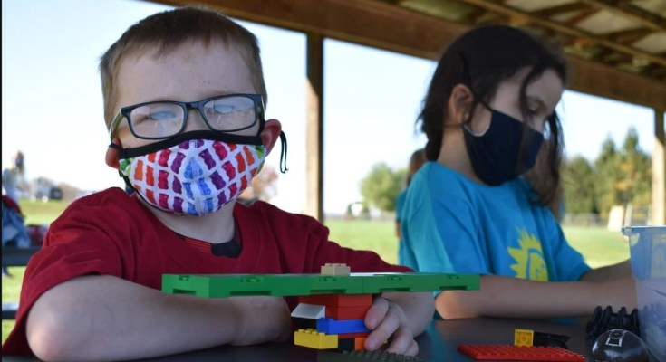 Child at camp in mask