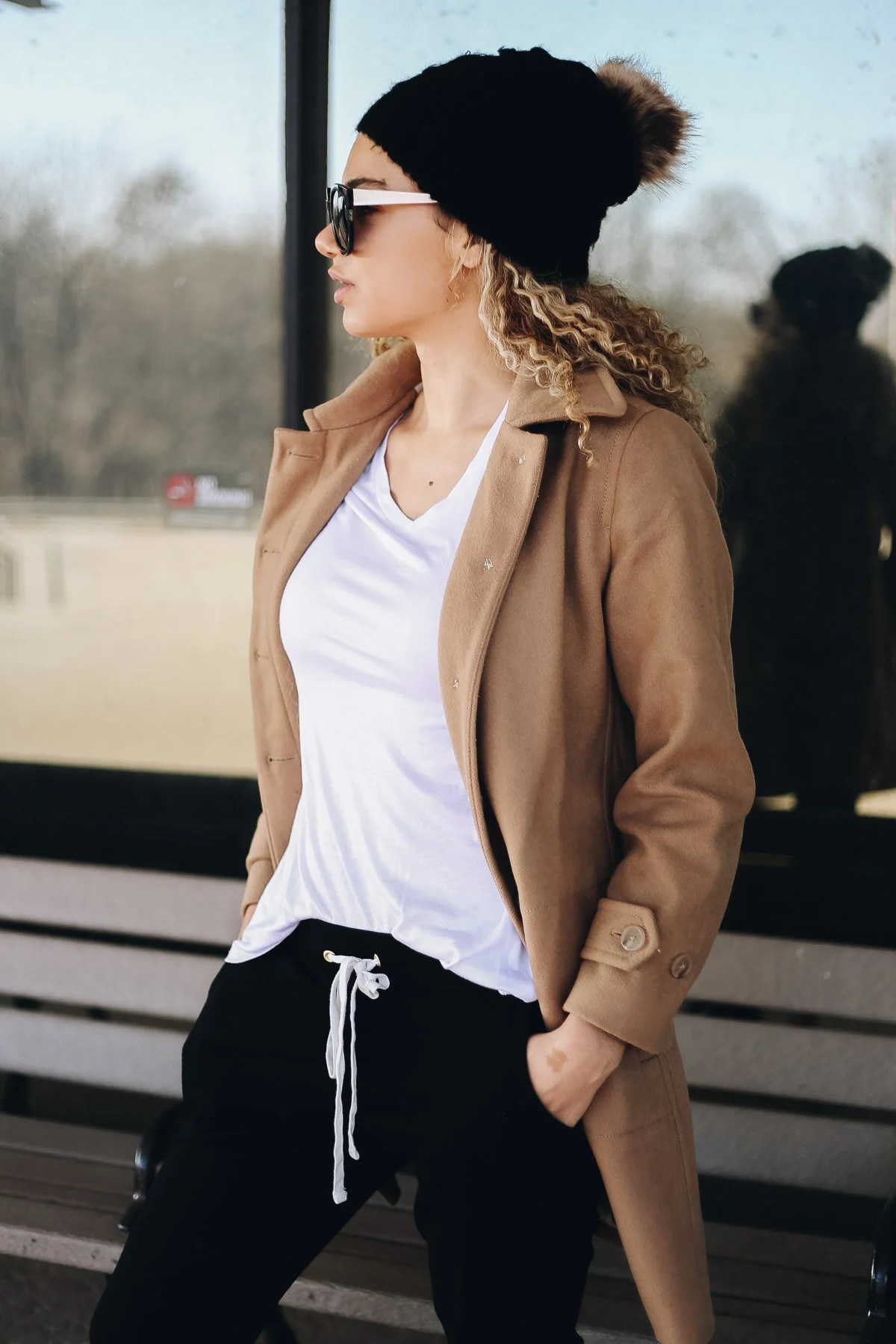 comfy airport outfit with joggers and a camel coat