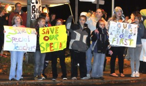 More than 100 people rallied outside the Tuttle House Board of Education building Monday night, drawing honks from cars passing by.