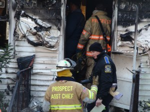 Prospect Mayor and Assistant Fire Chief Bob Chatfield discusses Wednesday's fire with a state police investigator; a home at 62 Summit Road caught fire early Wednesday morning and claimed one life.