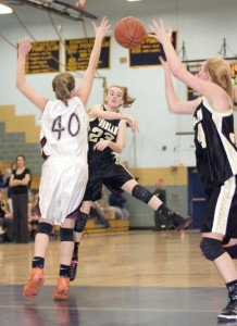 Woodland junior guard Lindsay Feducia finds junior forward Heather Framski in the post for a layup in Monday's NVL semifinal vs. Torrington. The bucket cut the deficit to 43-42, but the Raiders pulled away with a 53-49 win.