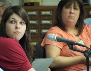 Sarah Hughes, a student leader of Woodland for Women Worldwide, and Region 16 Board of Education member Donna Cullen listen to the organization's co-founder, Lisa Olivere, during a school board meeting Wednesday at Long River Middle School.