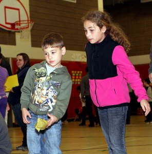 Haley Wolfanger, 9, and Aidan Wolfanger, 6, compete in the home run beanbag toss.