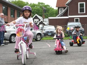 From left Hannah DeCampos, Alivia Stewart, and Matthew DosSantos trike around the parking lot of Tender Years Preschool in Naugatuck during the annual Trike-a-Thon May 20.