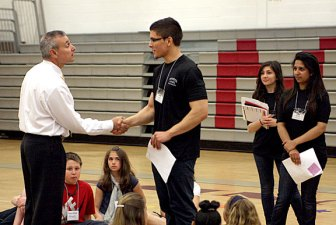 Naugatuck High School Principal Fran Serratore, left, demonstrates proper handshaking technique with Sebastian Correa.
