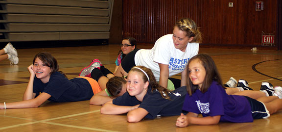 Alexis Granahan, top, lays across some of her campers as part of a serving exercise at the Parks and Recreation Department sponsored volleyball camp at Naugatuck High School July 14.
