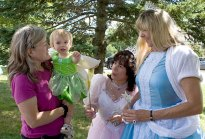 From left, Barbara Rowe with her 20-month-old granddaughter Fallon Rowe, Cher Brooks, as Cinderella, and Monica Robinson as Glinda, dressed up for character day at End of Summer Fun Week on the Prospect Town Green Aug. 22. The day featured face painting, train rides, and ice cream.