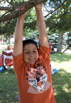 Jaxon Grim, 9, hangs from a tree during End of Summer Fun Week on the Prospect Town Green Aug. 22. Monday was character day and featured face painting, train rides, and ice cream.