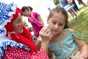 Mary 'Lollipop' Toma, with Party Troupe, paints the face of Laura Grim, 5, during End of Summer Fun Week on the Prospect Town Green Aug. 22. Monday was character day and featured face painting, train rides, and ice cream.