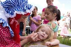 """Mary """"Lollipop"""" Toma, with Party Troupe, paints the face of Caitlyn Fitzmorris, 3, during End of Summer Fun Week on the Prospect Town Green Aug. 22. Monday was character day and featured face painting, train rides, and ice cream."""