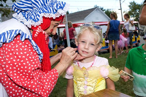 """Mary """"Lollipop"""" Toma, with Party Troupe, paints the face of Laura DeGennaro, 4, during End of Summer Fun Week on the Prospect Town Green Aug. 22. Monday was character day and featured face painting, train rides, and ice cream."""